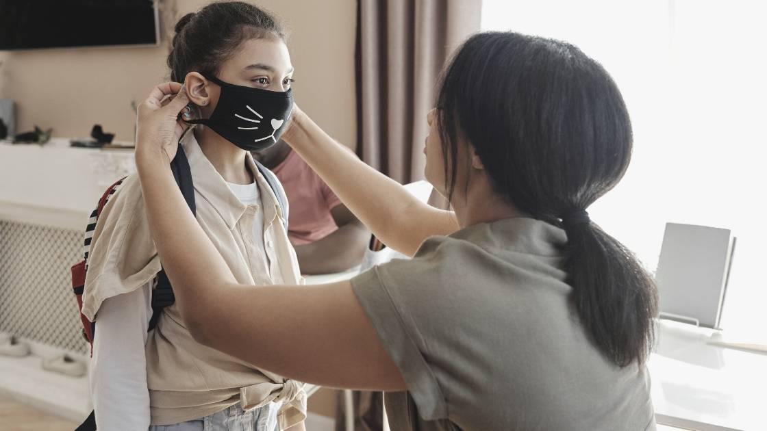 woman putting mask on child